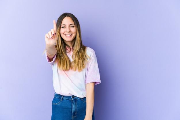 Молодая кавказская женщина, изолированные на фиолетовом фоне, показывая номер один пальцем.