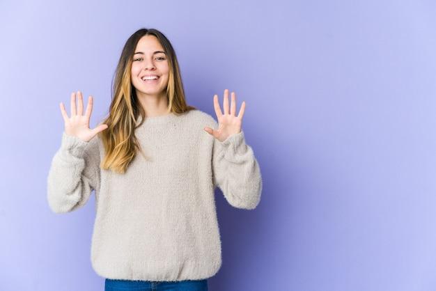 Молодая кавказская женщина, изолированные на фиолетовом фоне, показывая номер десять руками.
