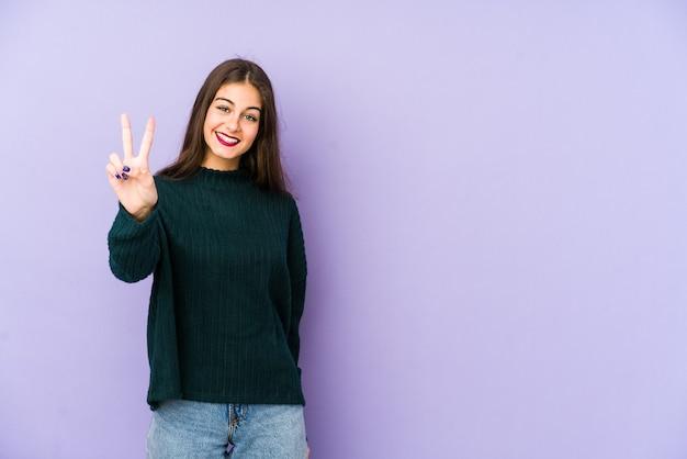 손가락으로 2 번을 보여주는 보라색 배경에 고립 된 젊은 백인 여자.