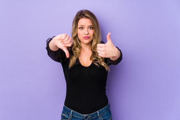 親指を上と親指を下に示す紫色の背景に分離された若い白人女性、難しい選択の概念