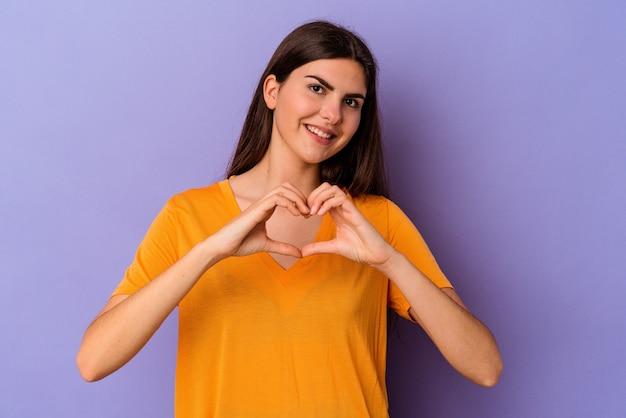 笑顔と手でハートの形を示す紫色の背景に分離された若い白人女性。