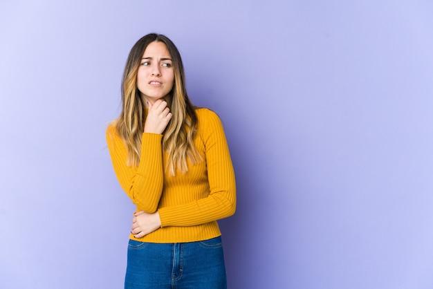 紫色の背景に分離された若い白人女性は、ウイルスや感染症のために喉の痛みに苦しんでいます。