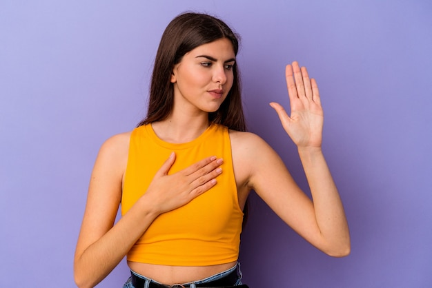 젊은 백인 여자는 가슴에 손을 넣어 선 서를 복용하는 보라색 배경에 고립.
