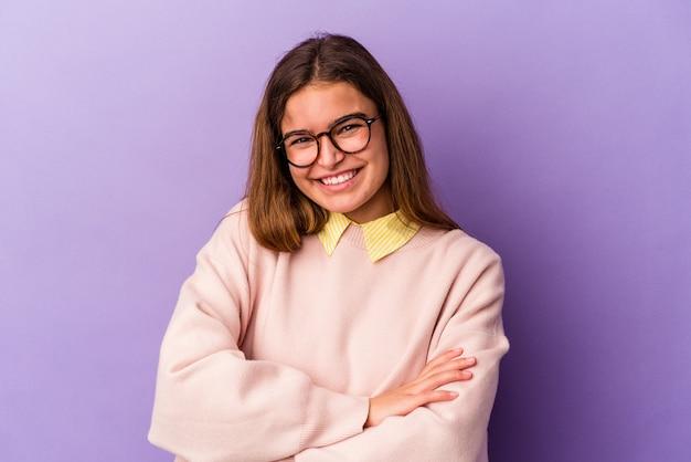 自信を持って、決意を持って腕を組んで、紫色の背景に孤立した若い白人女性。