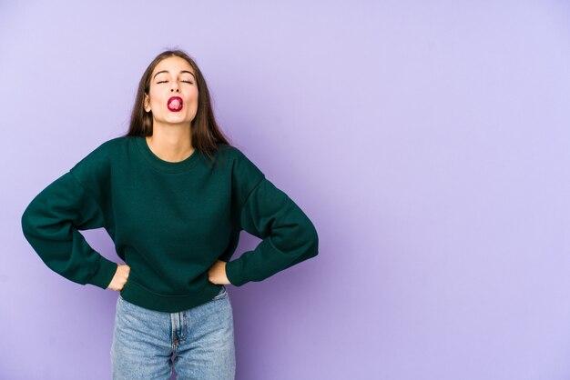 Молодая кавказская женщина изолирована на фиолетовом смешном и дружелюбном торчащем языке.