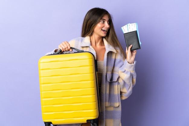 スーツケースとパスポートと休暇で紫に分離された若い白人女性