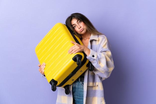 旅行スーツケースと不幸な休暇で紫に孤立した若い白人女性