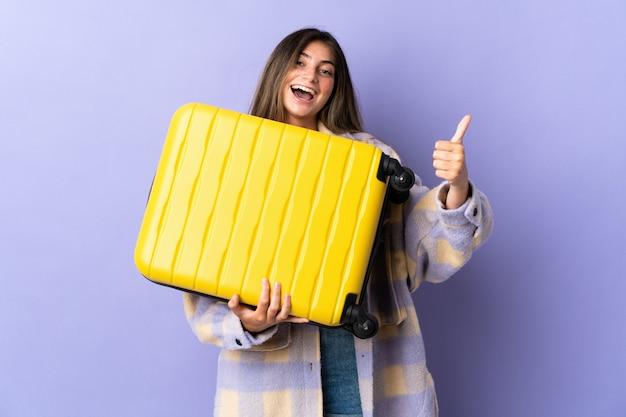 旅行スーツケースと親指を上にして休暇で紫に分離された若い白人女性