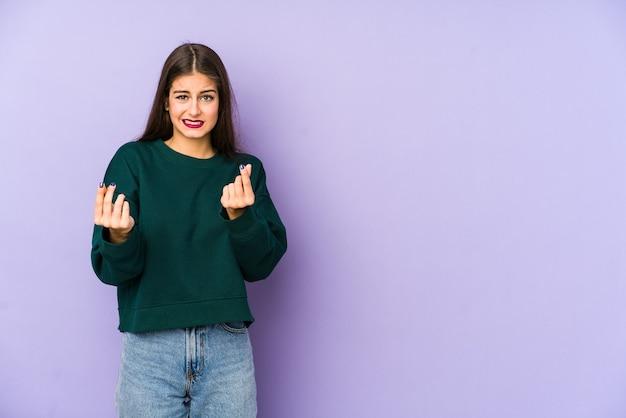 彼女がお金を持っていないことを示す紫色で隔離された若い白人女性。