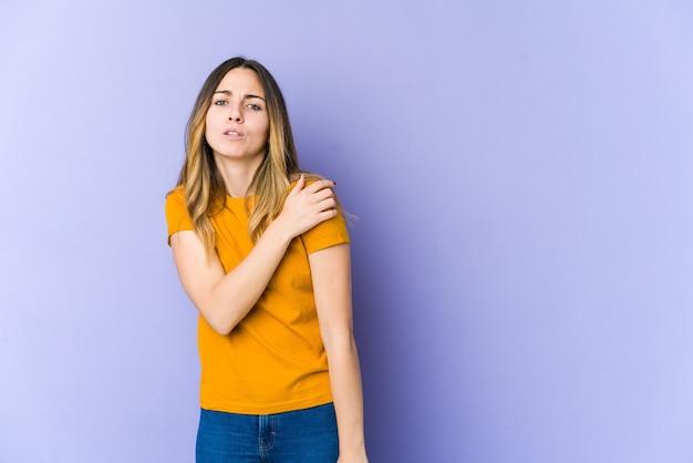 肩の痛みを抱えている紫色の空間に孤立した若い白人女性。