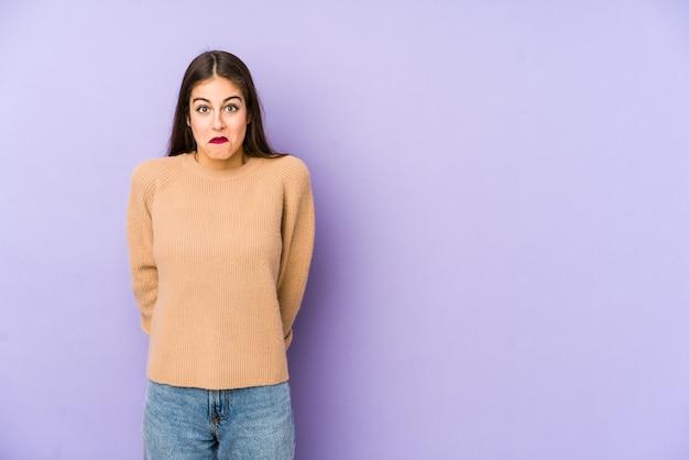紫色の空間に孤立した若い白人女性は肩をすくめ、目を開けて混乱しました。