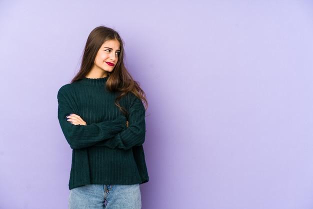 Молодая кавказская женщина изолирована на фиолетовом, подозрительно, неуверенно, исследуя вас.