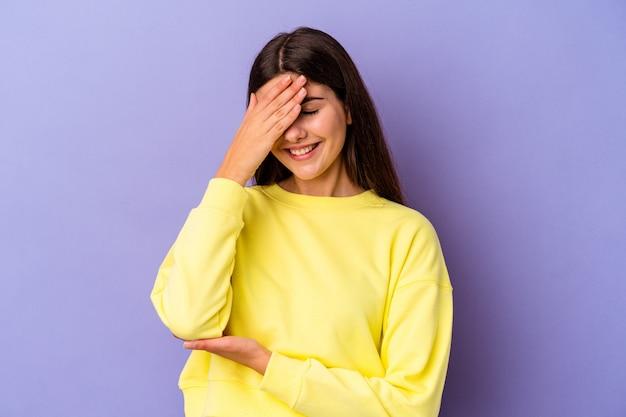 紫色の壁に孤立した若い白人女性が指で瞬き、恥ずかしそうに顔を覆っている。