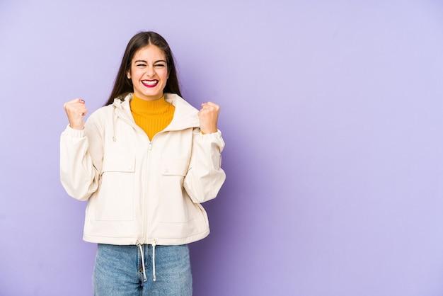 のんびりと興奮して応援する紫色の壁に孤立した若い白人女性。勝利の概念。