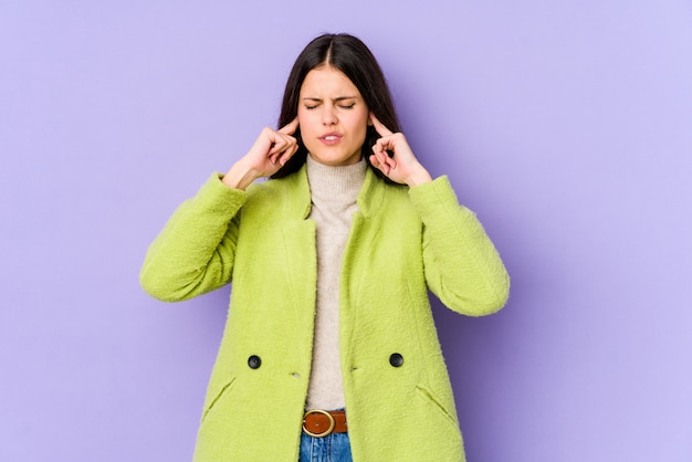 Молодая кавказская женщина изолированная на фиолетовой стене покрывая уши с пальцами, усиленный и отчаянный громко окружающим.