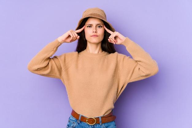 紫色の壁に分離された若い白人女性は、人差し指を指して頭を保ち、タスクに焦点を当てた。