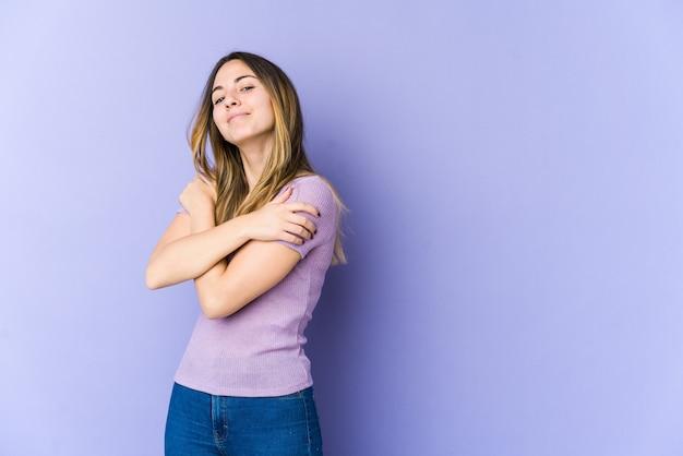 Молодая кавказская женщина, изолированная на фиолетовых стенах, обнимает, беззаботно улыбаясь и счастливо.