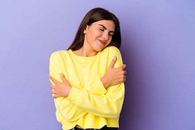 보라색 벽 포옹에 고립 된 젊은 백인 여자, 평온하고 행복 미소