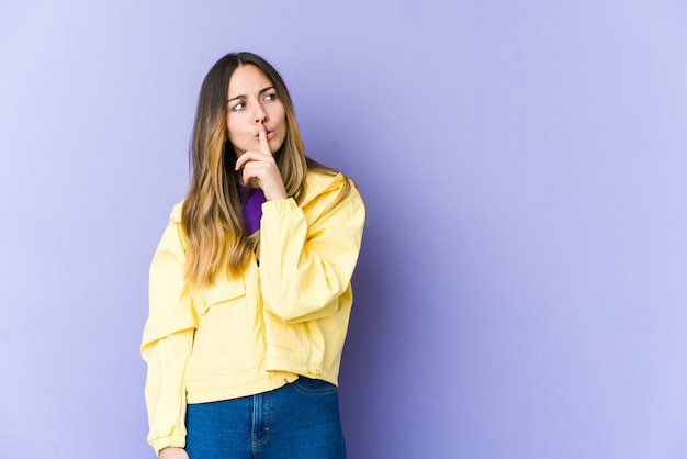 Молодая кавказская женщина изолирована на фиолетовой стене, сохраняя секрет или прося тишины.
