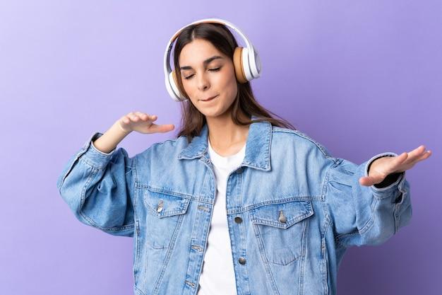 Молодая кавказская женщина изолирована на фиолетовой стене, слушает музыку и танцует