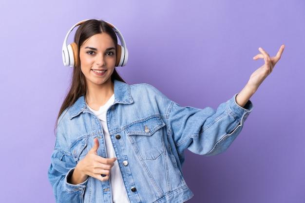 音楽を聴き、ギターのジェスチャーをしている紫色の壁に孤立した若い白人女性