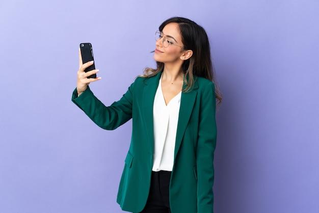 Selfie를 만드는 보라색 벽에 고립 된 젊은 백인 여자