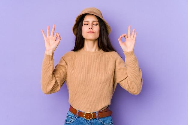 紫色の壁に分離された若い白人女性は懸命に仕事をした後リラックスし、ヨガを行っています。