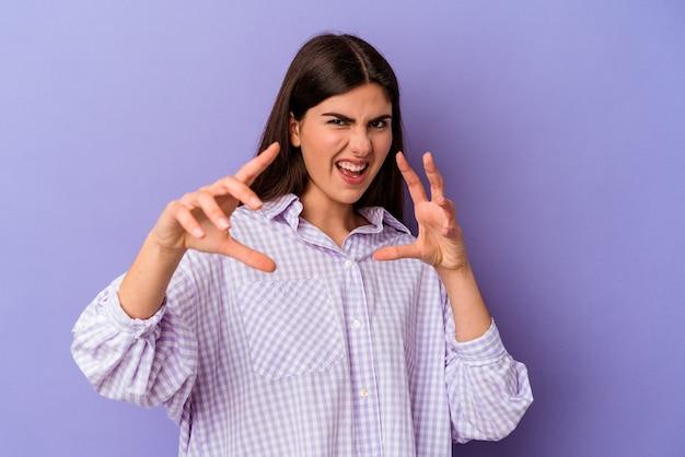 猫を模倣した爪、攻撃的なジェスチャーを示す紫色の壁に分離された若い白人女性