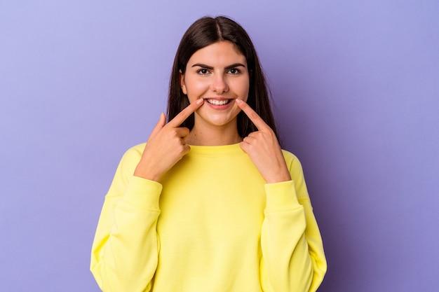 입에 손가락을 가리키는 보라색 벽 미소에 고립 된 젊은 백인 여자.