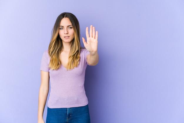 紫色の壁に孤立した若い白人女性が一時停止の標識を示している手を伸ばして立って、あなたを妨げています。