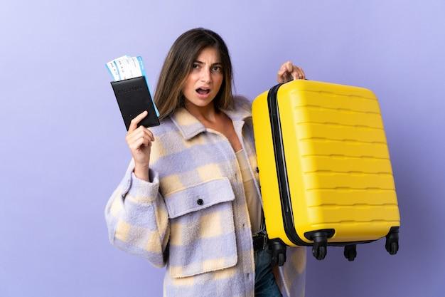 Молодая кавказская женщина изолирована на фиолетовой стене несчастной в отпуске с чемоданом и паспортом