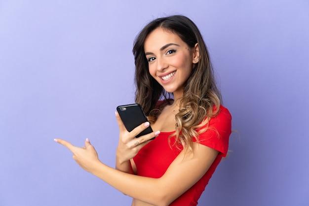 Молодая кавказская женщина изолирована на фиолетовой стене, используя мобильный телефон и указывая назад