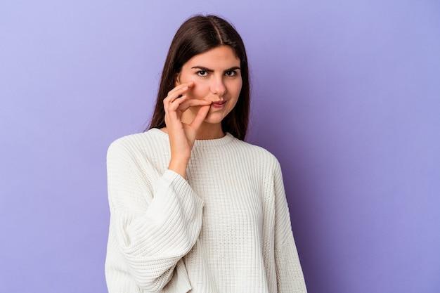 비밀을 유지하는 입술에 손가락으로 보라색 벽에 고립 된 젊은 백인 여자