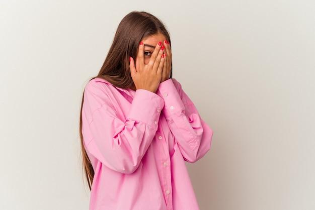 白い背景で隔離された若い白人女性は、おびえ、神経質な指を点滅します。