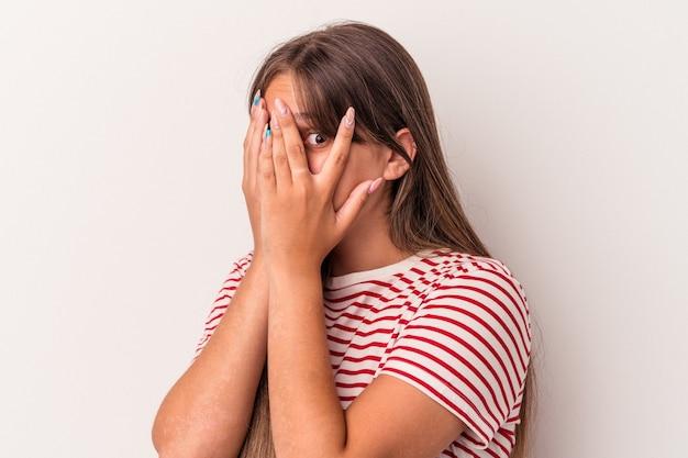 白い背景で隔離の若い白人女性は、おびえ、神経質な指を点滅します。