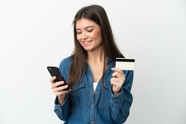 신용 카드로 모바일로 구매하는 흰색 배경에 고립 된 젊은 백인 여자