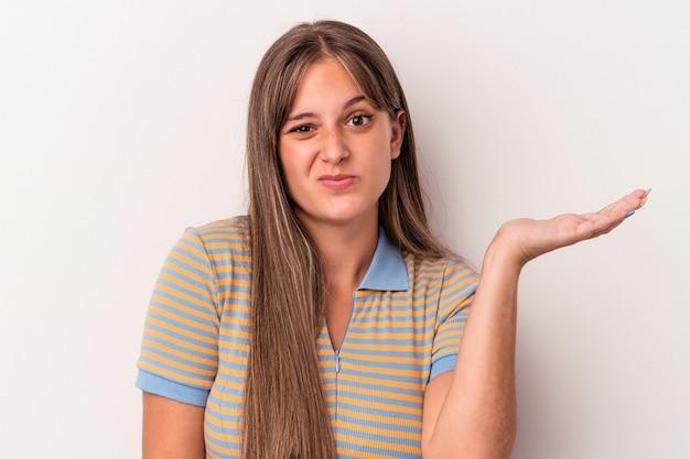 白い背景に孤立した若い白人女性は、ジェスチャーを疑って肩をすくめる。