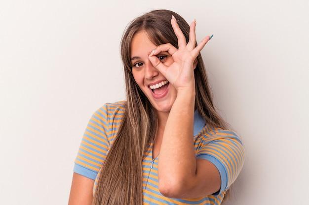 白い背景で隔離の若い白人女性は、目に大丈夫なジェスチャーを維持して興奮しました。