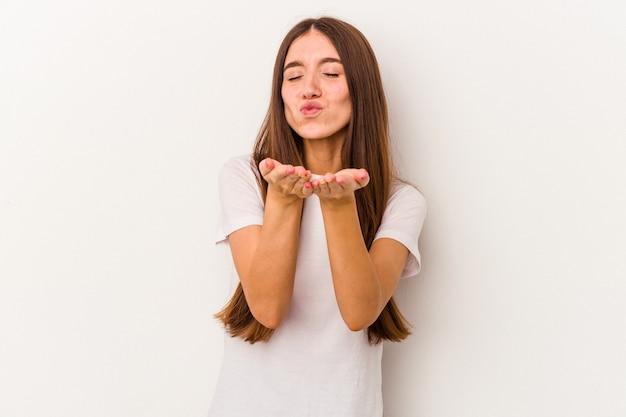 唇を折り、手のひらを持って空気のキスを送信する白い背景で隔離の若い白人女性。