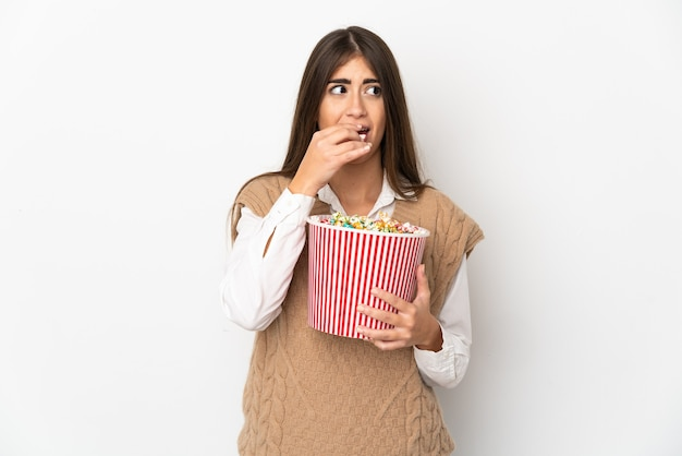 ポップコーンの大きなバケツを保持している白い背景で隔離の若い白人女性