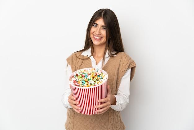 Молодая кавказская женщина изолирована на белом фоне, держа большое ведро попкорна