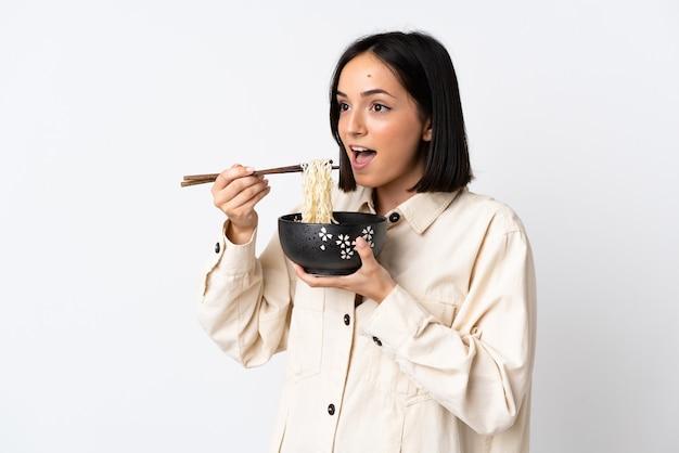 Молодая кавказская женщина, изолированная на белом фоне, держит миску лапши с палочками для еды и ест ее