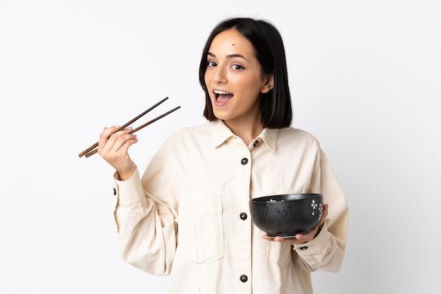 箸で麺のボウルを保持している白い背景で隔離の若い白人女性