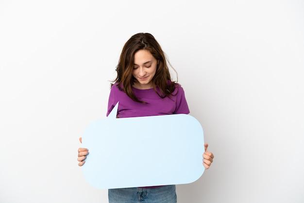 Молодая кавказская женщина изолирована на белом фоне, держа пустой речевой пузырь
