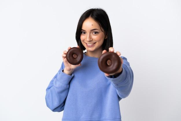 幸せな表情でドーナツを保持している白い背景で隔離の若い白人女性