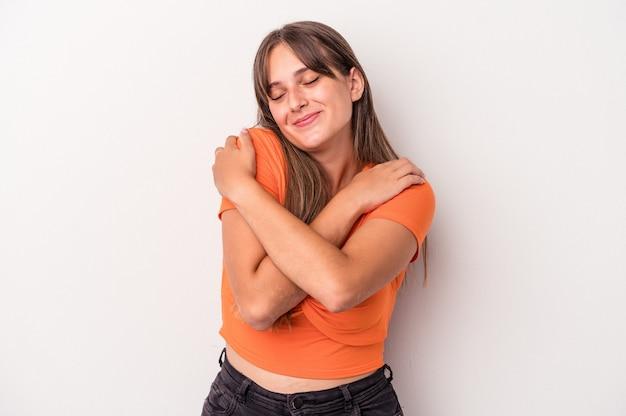 白い背景で隔離の若い白人女性は、のんびりと幸せな笑顔を抱きしめます。