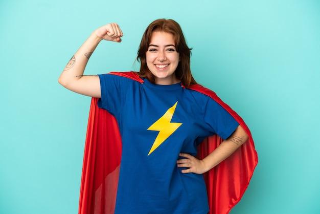 Молодая кавказская женщина изолирована на белом фоне в костюме супергероя и делает сильный жест