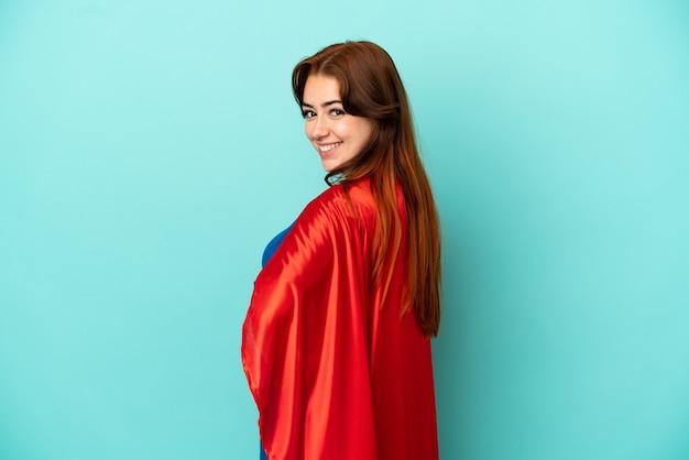 Молодая кавказская женщина изолирована на белом фоне в костюме супергероя и позирует с руками на бедрах и улыбается