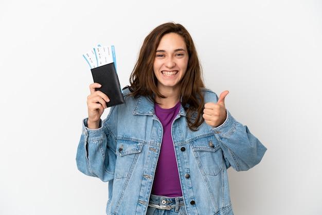 Молодая кавказская женщина изолирована на белом фоне в отпуске, держа паспорт и самолет с большим пальцем вверх