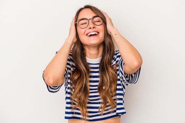 흰색 배경에 격리된 젊은 백인 여성은 머리에 손을 얹고 즐겁게 웃고 있습니다. 행복 개념입니다.